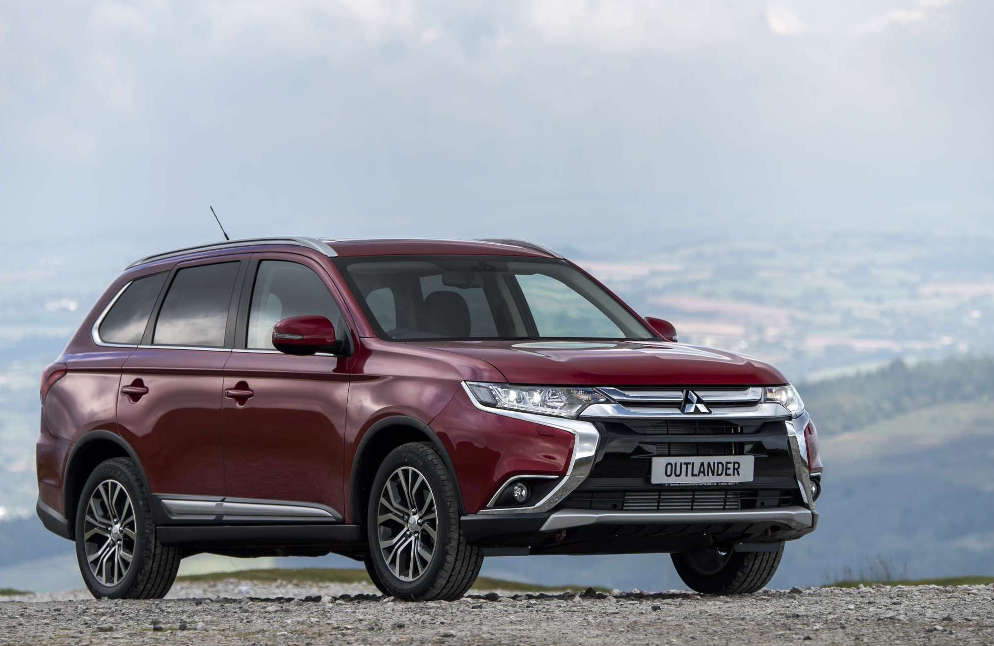 Maroon Mitsubishi Outlander parked overlooking a countryside view