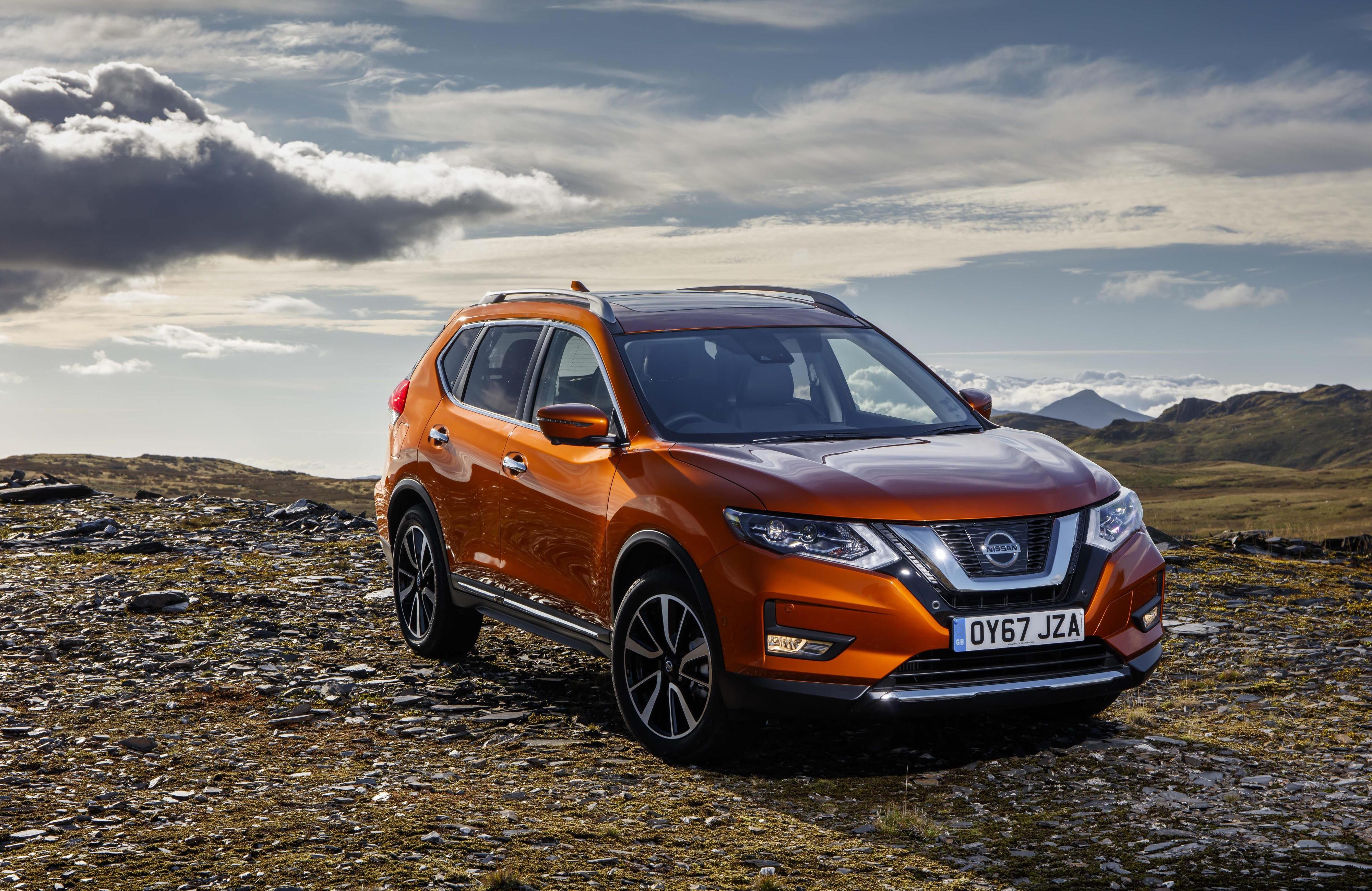 Amber Nissan X-Trail parked on a mountain range.