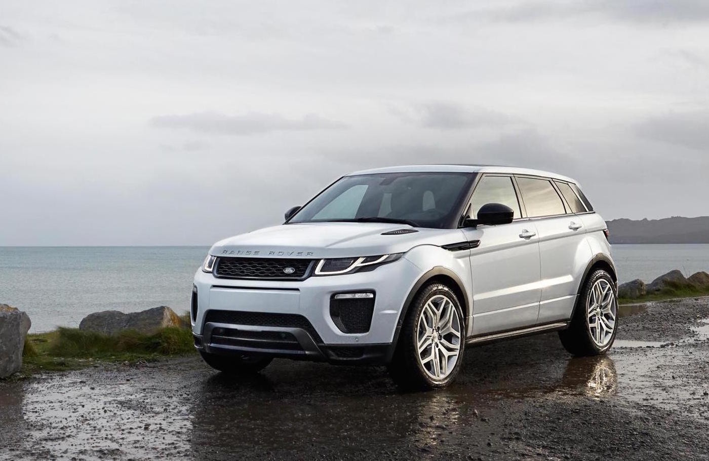 White Range Rover Evoque parked overlooking a lake view.