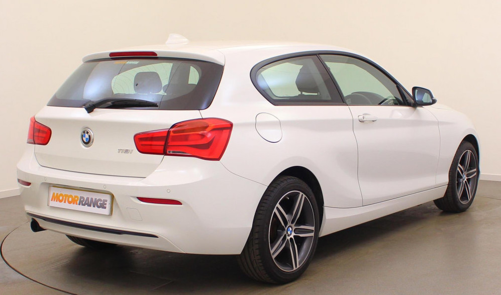 Rear-side view of white BMW 1 Series parked in showroom