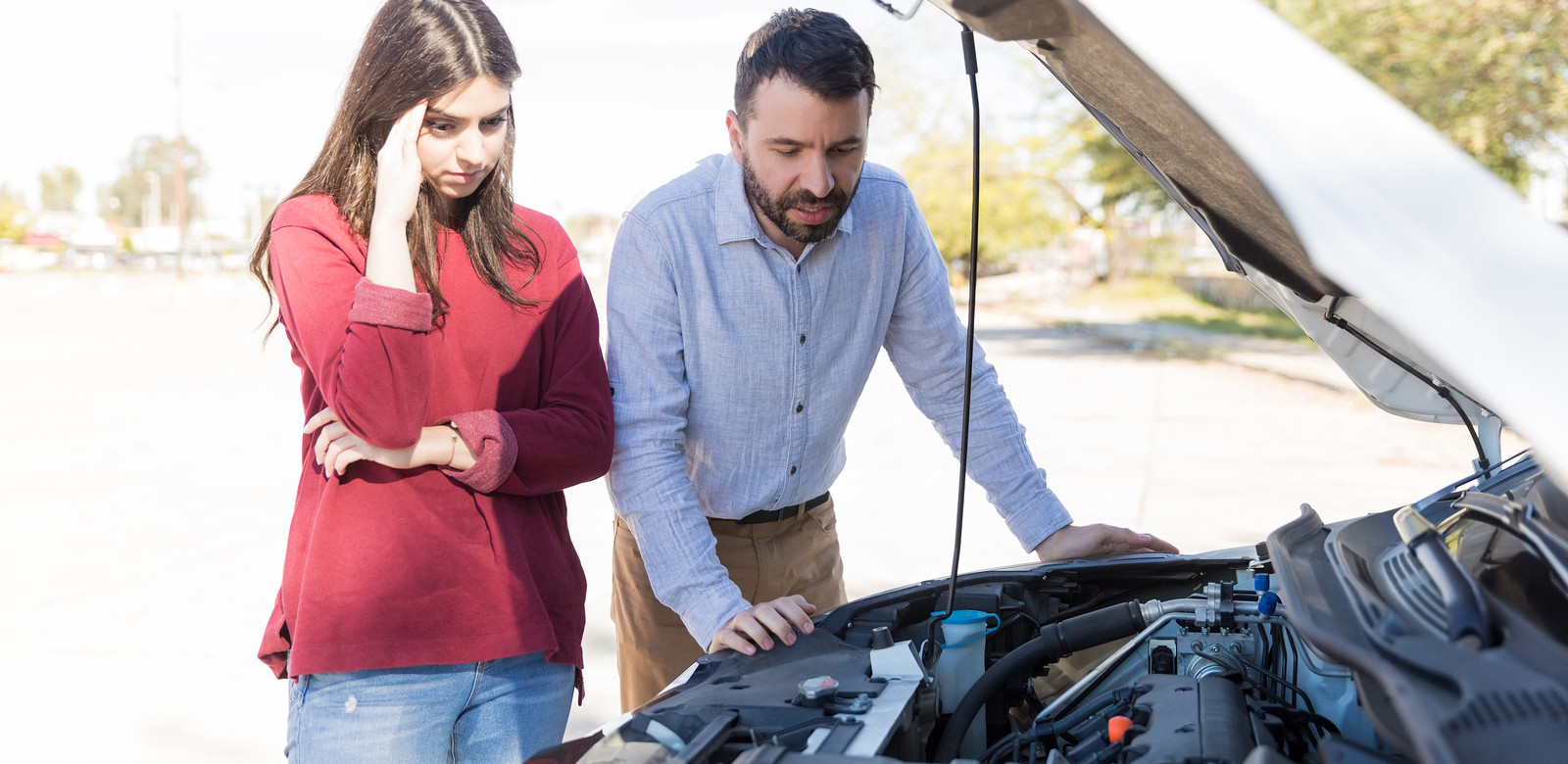 Worried-looking lady and bearded man staring at car engine