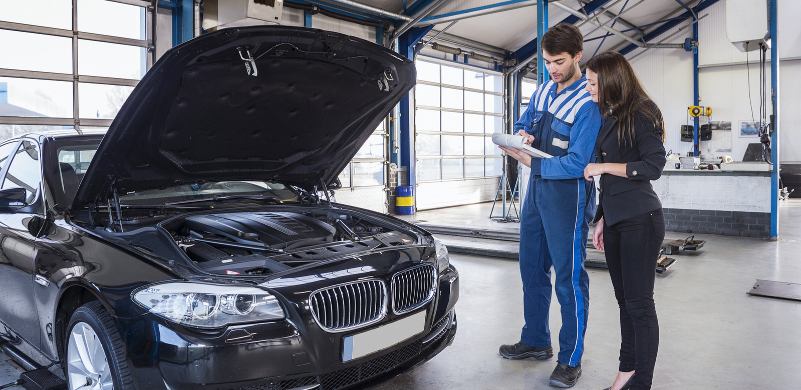 Mechanic with clipboard and and female customer standing to right of black BMW with bonnet open.