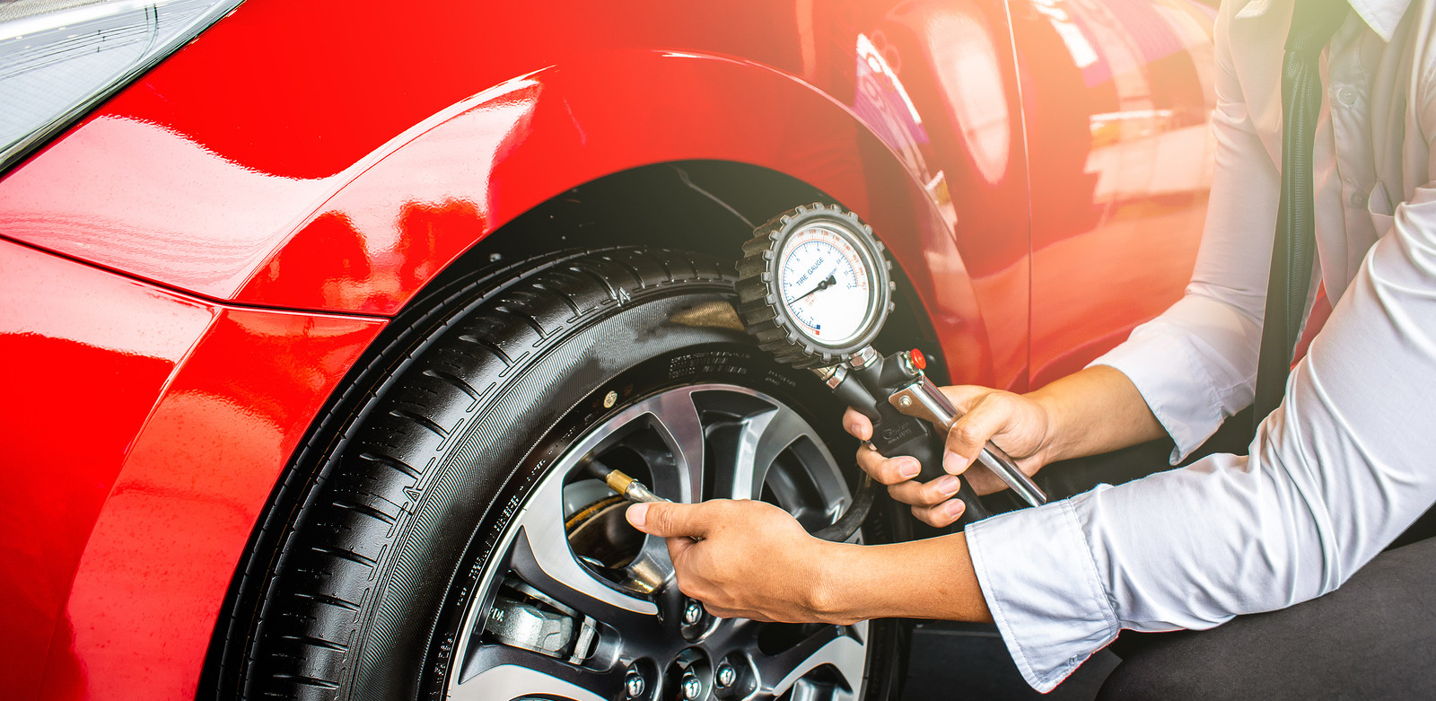 Man in long shirt sleeves checking tyre of red car with pressure gauge.