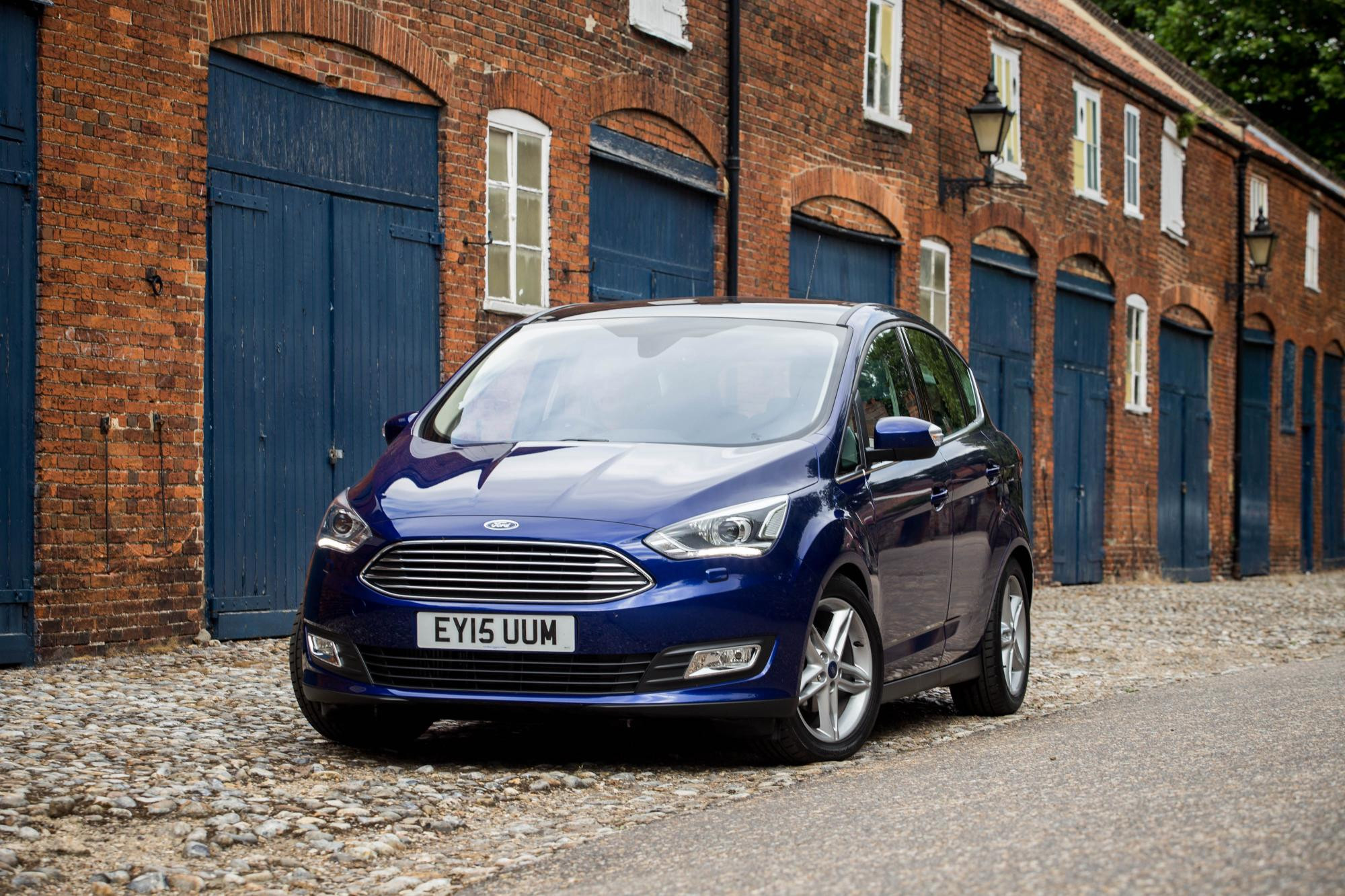 Blue Ford C-Max parked facing front on a cobbled street in front of a row of workshops
