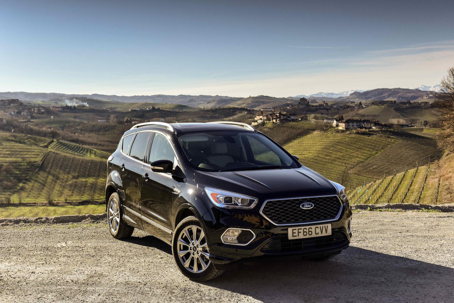 Black Ford Kuga parked facing three-quarters overlooking countryside.