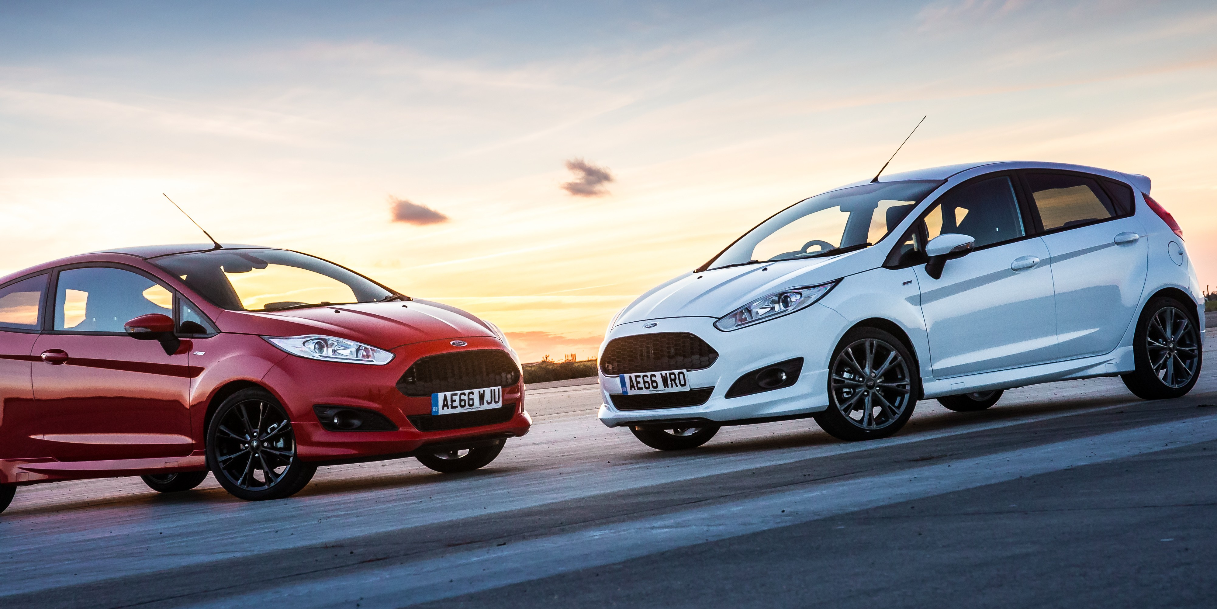 Red Ford Fiesta on left and white Ford Fiesta on right, nose to nose, with sunset in background
