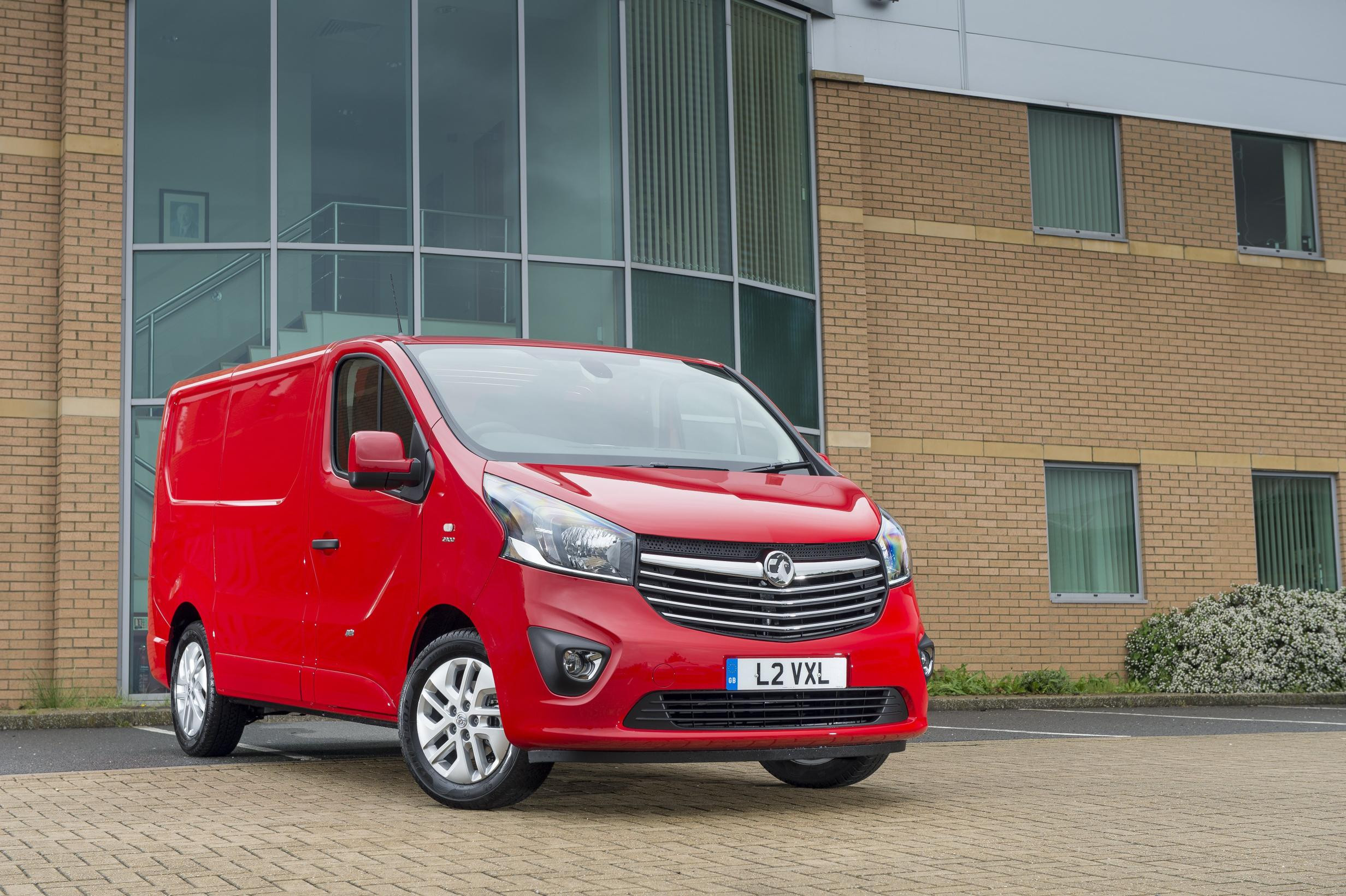 Red Vauxhall Vivaro parked in front of office unit, facing right